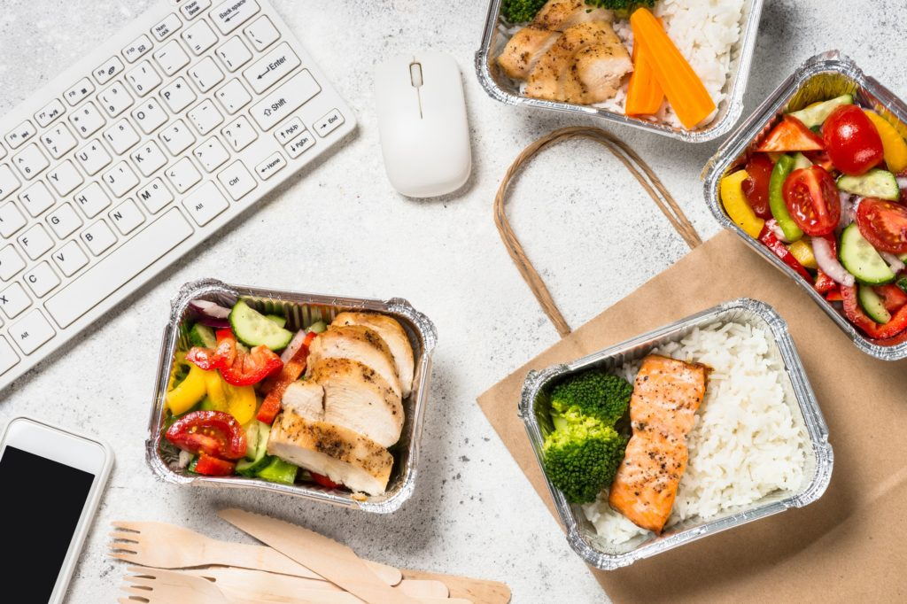 Food delivery concept - healthy lunch in boxes in the office