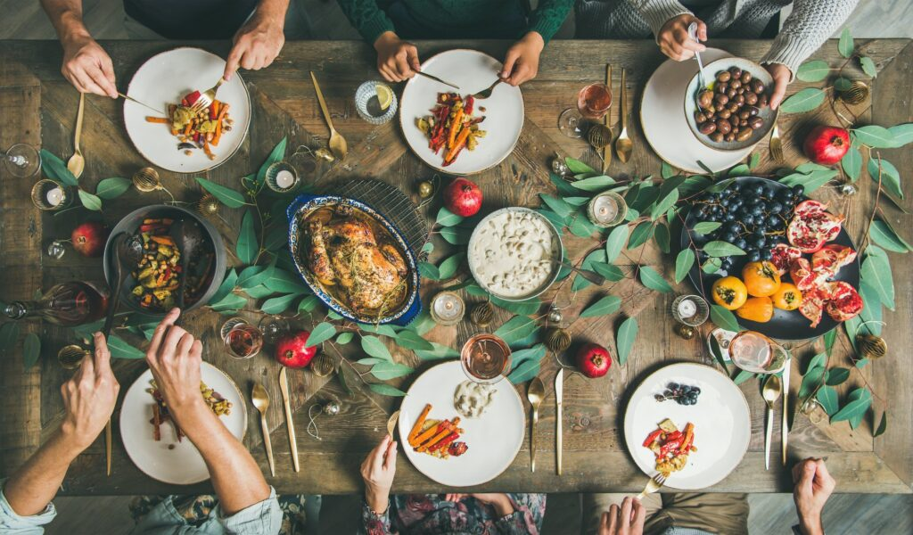 Friends or family eating at festive Christmas table, top view